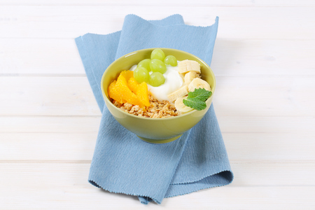bowl of muesli with white yogurt and fresh fruit on blue place mat Stock Photo