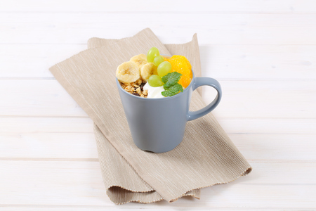 cup of muesli with yogurt and fresh fruit on beige place mat