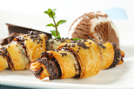 filled roll: detail of chocolate chip croissants with scoop of ice cream on white plate Stock Photo