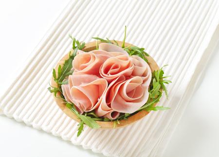 bowl of fresh arugula salad with sliced ham on white place mat Stock Photo