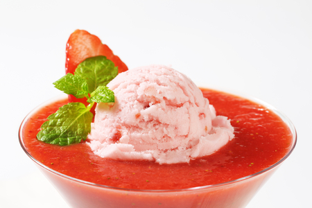 Ice cream with strawberry puree in stemmed glass