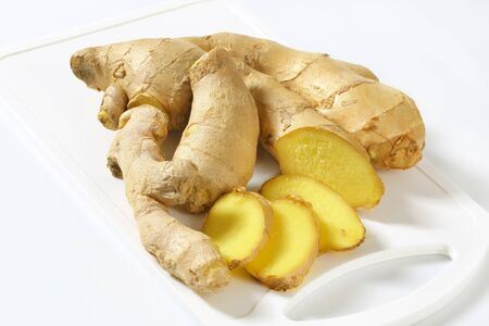 Fresh ginger root on white plastic cutting board Stock Photo