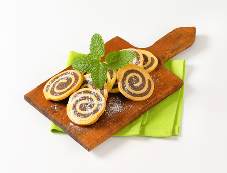 sweet chocolate rolls on wooden cutting board Stock Photo