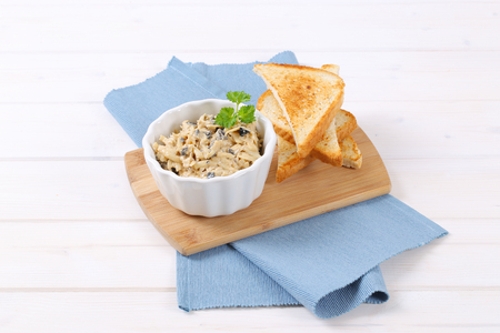 bowl of grated cheese spread with olives and toast on wooden cutting board