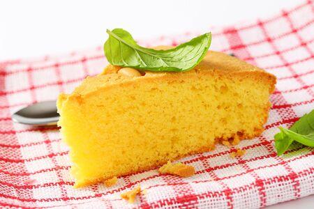 Slice of lemon sponge cake on checked tea towel