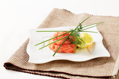Closeup of salmon tartare garnished with chives and dill