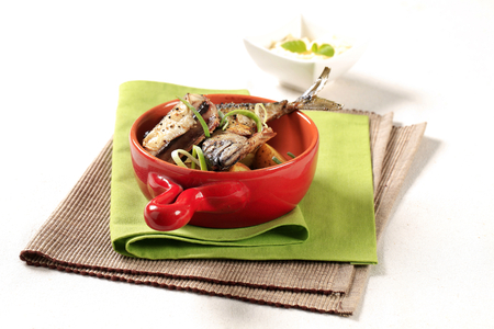 Spiced mackerel with roasted potatoes in a red pan