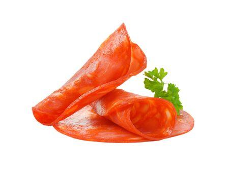 slices of chorizo salami with parsley on white background Stock Photo