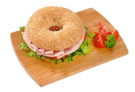sesame bagel sandwich with ham on wooden cutting board