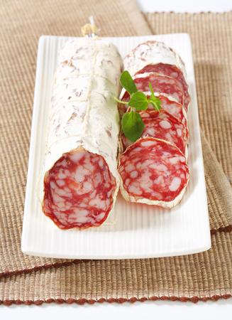 Sliced French Saucisson Sec on long white plate Фото со стока - 80711994