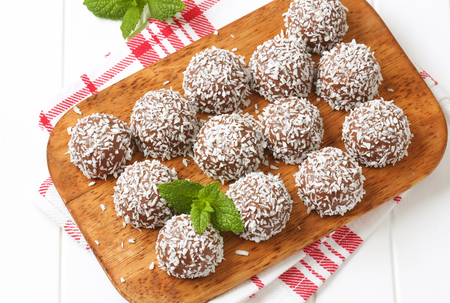 Chocolate coconut balls on cutting board Stock Photo