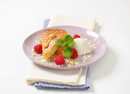 Slice of almond cake with ice cream and fresh raspberries