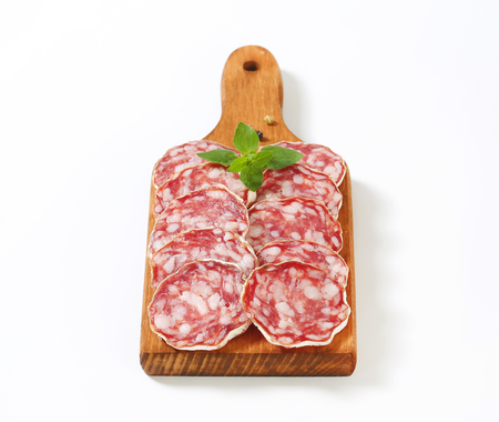 Sliced French dry sausage (Saucisson Sec)  on cutting board