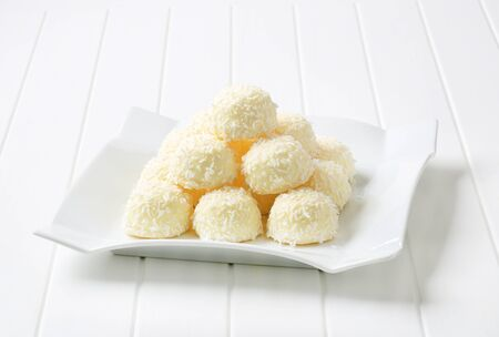 desiccated: Pile of coconut snowball truffles on square plate