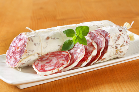 air dried: Sliced French Saucisson Sec on long white plate Stock Photo