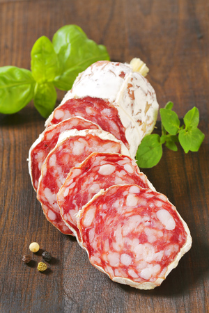 Sliced French Saucisson Sec on wooden background