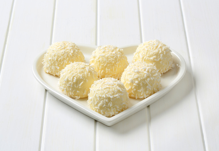 Coconut snowball truffles on heart-shaped plate Stock Photo