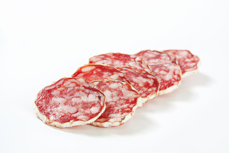 Sliced French dry sausage (Saucisson Sec)  on white background