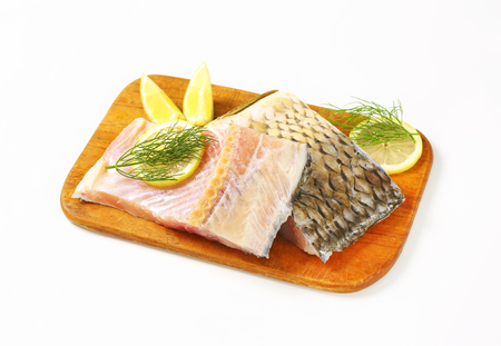 Raw carp fillets with lemon and dill on cutting board