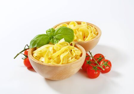 Cooked ribbon pasta in wooden bowls Reklamní fotografie