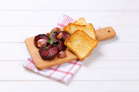 baked beetroot and garlic with toasted bread on wooden cutting board Stock Photo