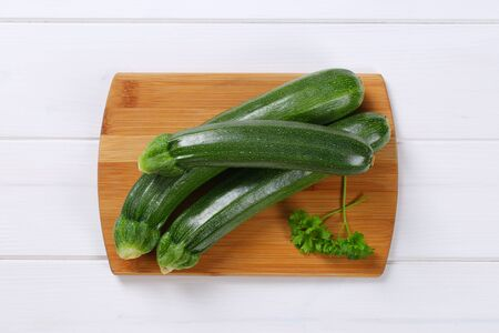 fresh green zucchini on wooden cutting board