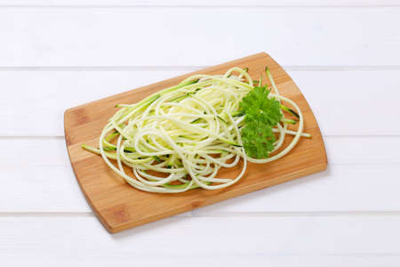 medula: heap of raw zucchini noodles on wooden cutting board