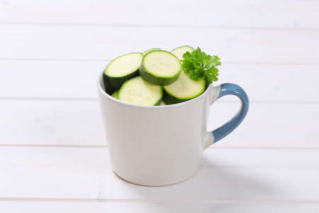 cup of green zucchini slices on white wooden background