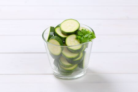 glass of green zucchini slices on white wooden background