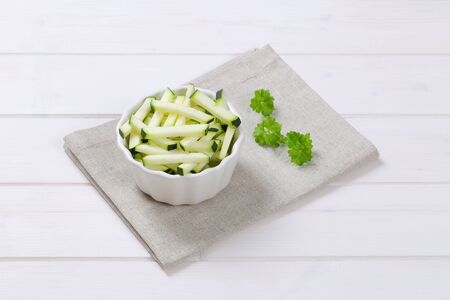 stripping: bowl of zucchini strips on beige place mat