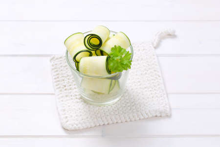 stripping: glass of raw zucchini strips on white table mat Stock Photo