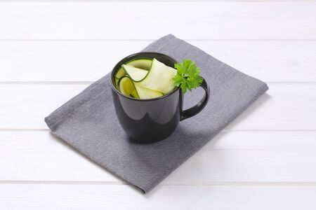 stripping: cup of raw zucchini strips on grey place mat Stock Photo