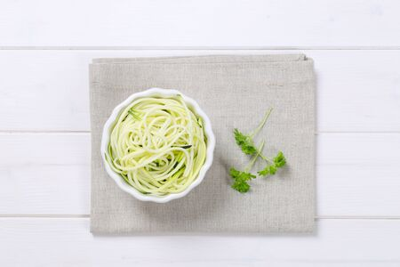bowl of raw zucchini noodles on beige place mat