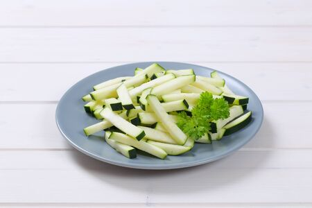 plate of zucchini strips on white wooden background