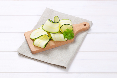 pile of raw zucchini strips on wooden cutting board Stock Photo