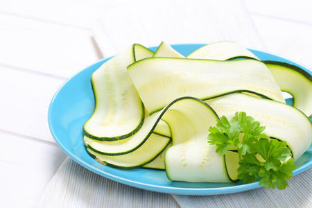 plate of raw zucchini strips on white place mat - close up Stock Photo