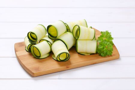 stripping: raw zucchini strips rolled on wooden cutting board