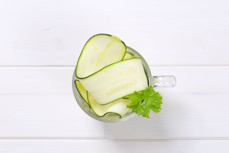 cup of raw zucchini strips on white wooden background