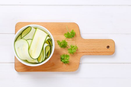 bowl of raw zucchini strips on wooden cutting board Stock Photo