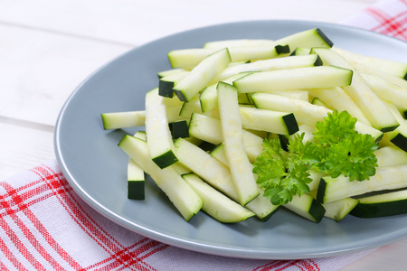 stripping: plate of zucchini strips on checkered dishtowel - close up Stock Photo