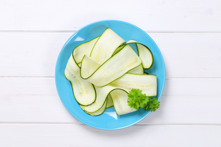 plate of raw zucchini strips on white wooden background