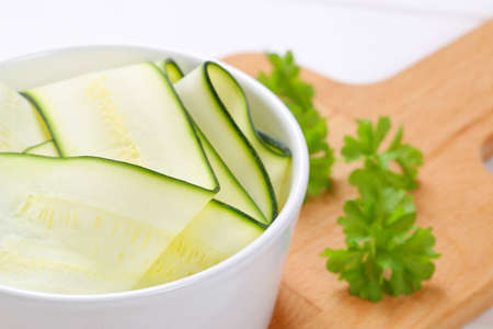 bowl of raw zucchini strips on wooden cutting board - close up Stock Photo