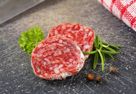 air dried: Slices of dry cured sausage with herbs and peppercorns on black cutting board Stock Photo