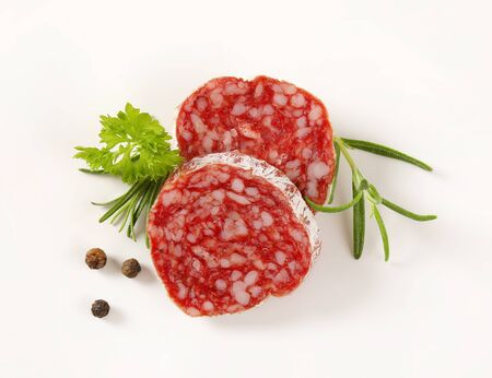 air dried: Slices of dry cured sausage with herbs and peppercorns on white background