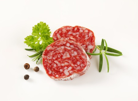 dry sausage: Slices of dry cured sausage with herbs and peppercorns on white background