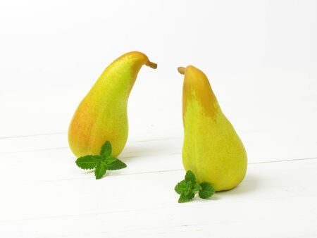luscious: two yellow pears on white wooden background