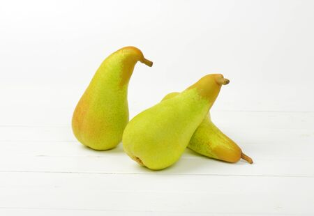 luscious: three yellow pears on white wooden background Stock Photo