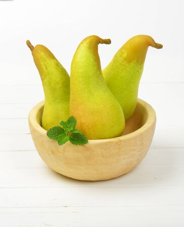 luscious: three yellow pears in wooden bowl