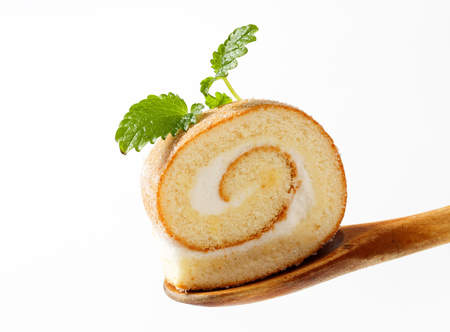 Slice of sweet creamy roll on a wooden spoon