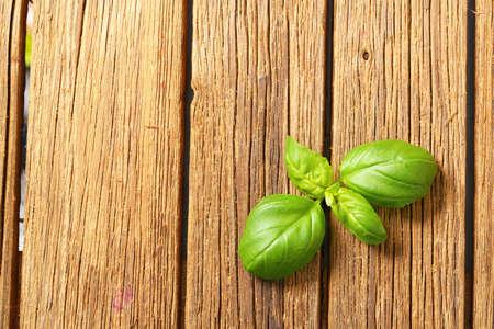 Fresh basil leaves on wooden table
